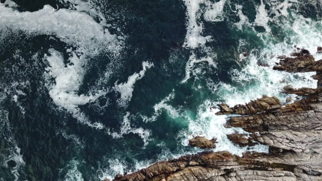aerial view over the waves crashing against the rocks - cliffs stock videos & royalty-free footage