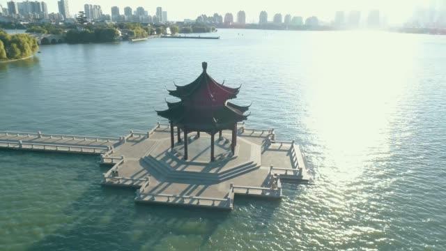 luftaufnahme über traditionelle chinesische antike pavillon auf dem see im sonnenuntergang, stadtansicht im hintergrund - pagode stock-videos und b-roll-filmmaterial