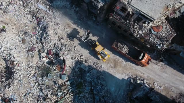 vídeos de stock e filmes b-roll de aerial view over trucks clearing up the destroyed buildings in the city aleppo. only rocks an dusts left after bombing in the civil war years in syria. - síria