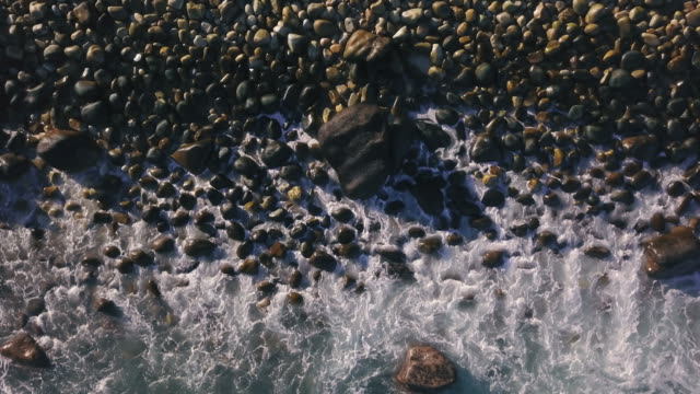 Aerial view over waves breaking on a rocky shore video