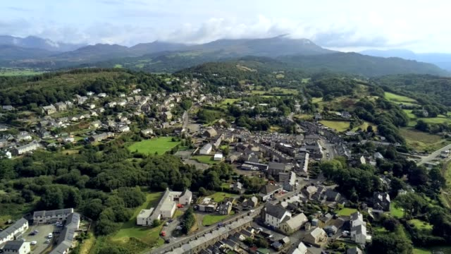 aerial view, pan move. drone panorama of penrhyndeudraeth town in snowdonia mountains in wales - osiedle mieszkaniowe filmów i materiałów b-roll