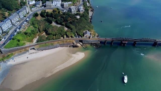 Vue aérienne, pan se déplacer. Panorama de drone sur la mer, pont, port, plage et ville de Barmouth, pays de Galles - Vidéo