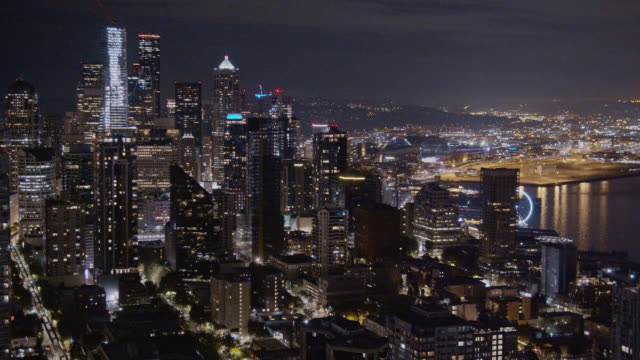 aerial view panning shot of the seattle skyline and puget sound (elliott bay) at night - урез воды стоковые видео и кадры b-roll