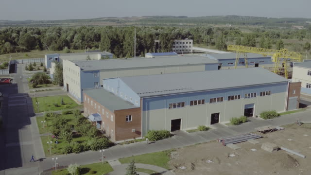 Aerial view park production plant. Manufacturing area in field drone view. Aerial top down view of modern technology manufacturing plant. Aerial footage of building new large industrial complex
