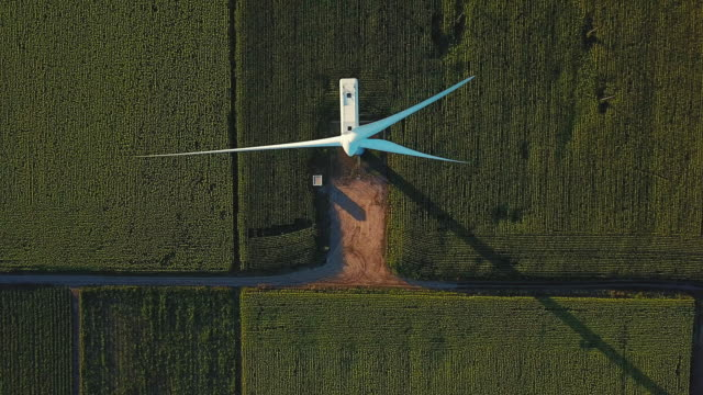 aerial view passing directly above a wind turbine in agricultural field - sustainability video stock e b–roll