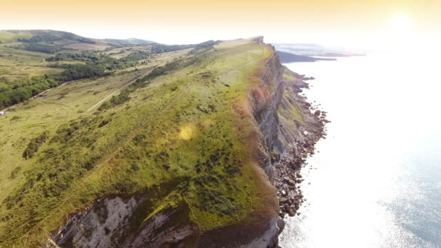 Aerial view past steep cliffs Aerial view over the sea past steep cliffs and rocky coastline and countryside at dawn country geographic area stock videos & royalty-free footage