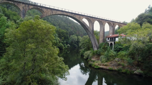 vídeos de stock e filmes b-roll de aerial view picturesque river with roman viaduct - douro