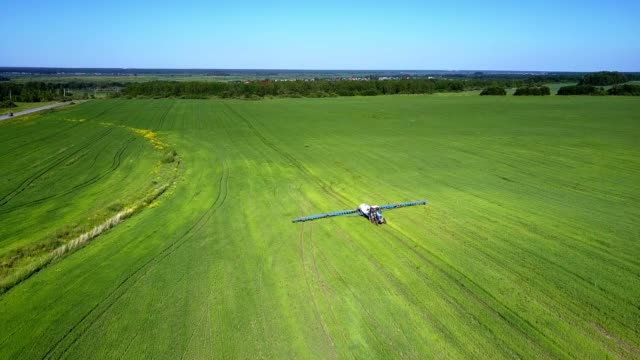 aerial view plain fields with trailed sprayer