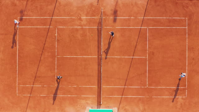Aerial view. Players are playing tennis on orange court Aerial view. Players are playing tennis on orange court teknik stock videos & royalty-free footage
