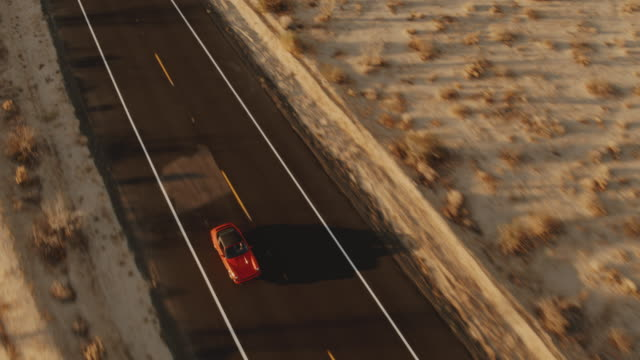 Aerial View Red Classic Car Driving Along Desolate Desert Road At Sunset