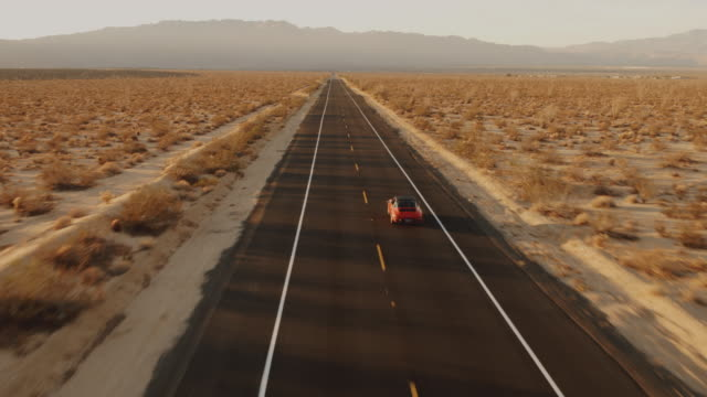 Aerial View Red Classic Car Driving Along Desolate Desert Road At Sunset video