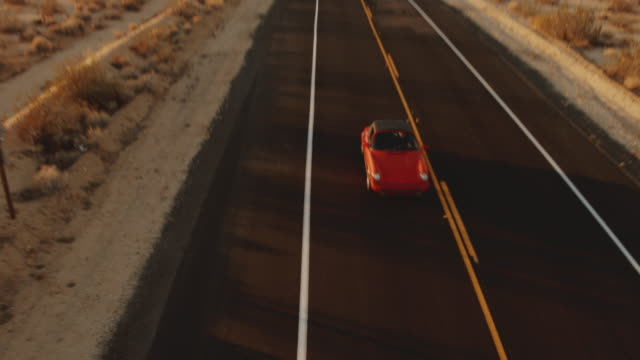 Aerial View Red Classic Car Driving Along Desolate Desert Road At Sunset Low flying aerial view of car driving on single lane highway in desert sports car stock videos & royalty-free footage