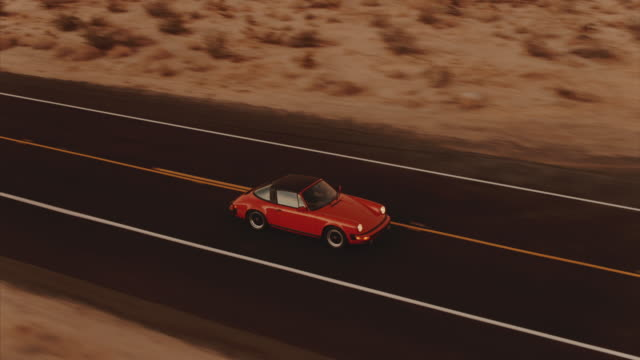 Aerial View Red Classic Car Driving Along Desolate Desert Road At Dusk With Headlights On Low flying aerial view of car driving along highway at dusk filmed with a drone sports car stock videos & royalty-free footage