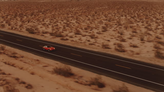 Aerial View Red Classic Car Driving Along Desolate Desert Road At Dusk With Headlights On