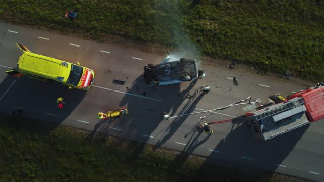 aerial view: rescue team of firefighters and paramedics work on a car crash traffic accident scene. preparing equipment, first aid help. saving injured and trapped people from the vehicle. zoom in - incidente video stock e b–roll