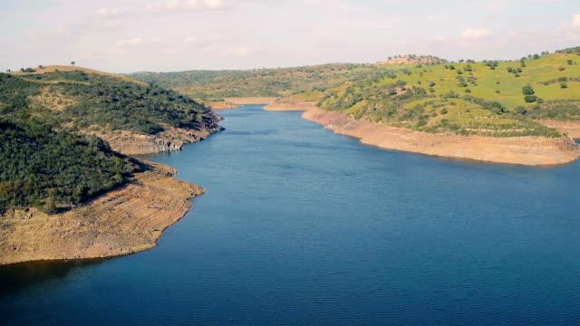 vídeos de stock e filmes b-roll de aerial view reservoir near dam - vídeos de barragem portugal