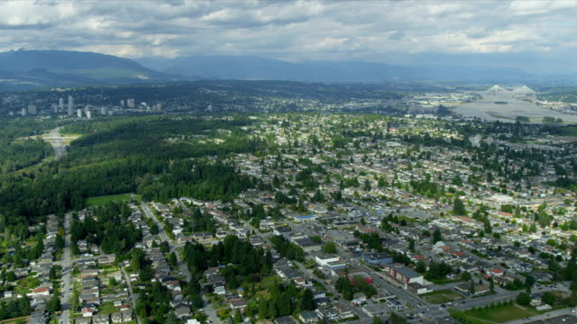 Aerial view residential suburbs New Westminster, Vancouver Aerial landscape view residential suburbs New Westminster District distant Fraser River and Port Mann suspension Bridge, British Columbia, Canada fraser river stock videos & royalty-free footage