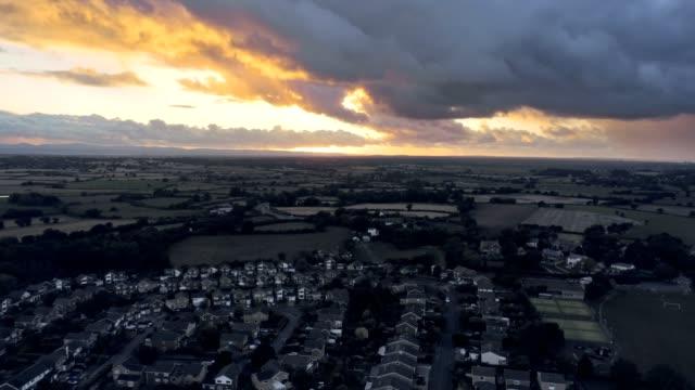 stockvideo's en b-roll-footage met luchtfoto, stijging omhoog verplaatsen. dramatische zonsondergang over woonwijk van stadje, tarvin in cheshire. - regen zon
