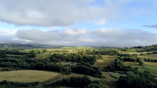 Aerial view, rise up move. Drone panorama of green fields near Llyn Celyn water reservoir in Wales. Traweryn river
