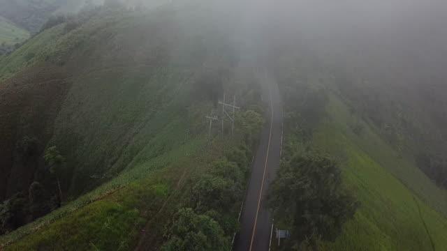 航空写真、移動中の車で森の霧の中を通り過ぎる道路、タイ北部 - 曲線点の映像素材/bロール