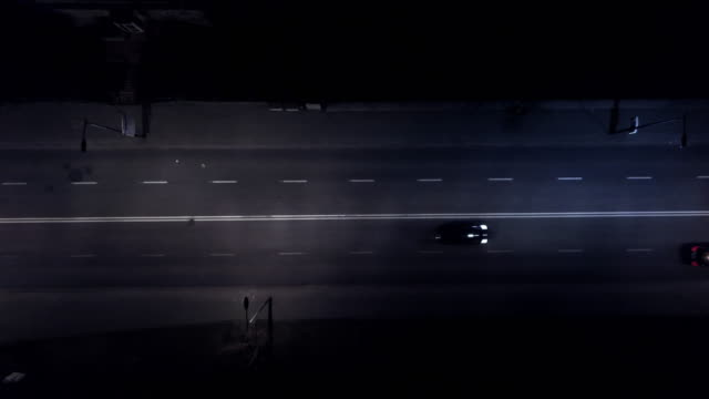 Aerial view road with cars in the night. Street lights. Raining. Cars passing by. Drone