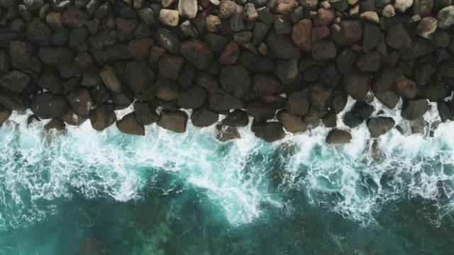 havadan görünüm-kıyı koruma siyah taşlar ve turkuaz renk okyanus. gran canaria, ispanya - dalgakıran stok videoları ve detay görüntü çekimi
