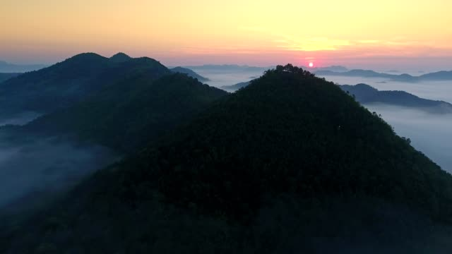 Aerial view shot by drone fly above a mountain range, slowly reveal the sun rises in the morning.