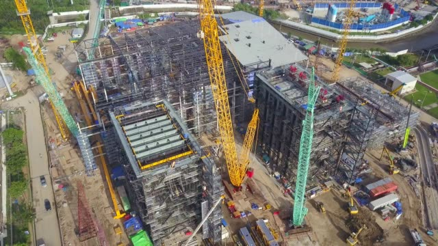 Aerial View shot of Combine cycle power plant Construction Site with tower crane, Mobile crane, Backhoe, Excavator and steel structure of boiler and cooling tower near river