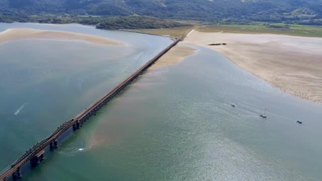 Vue aérienne, déplacement latéral. Panorama de drone sur montante marée mer, baie, ancré bateaux, acier pont ferroviaire à Barmouth, pays de Galles - Vidéo