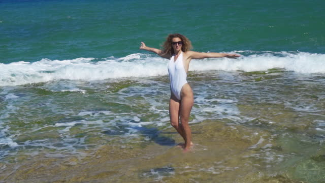Luftbild. Schlanke Frau tanzt auf felsigen Meer Strand – Video