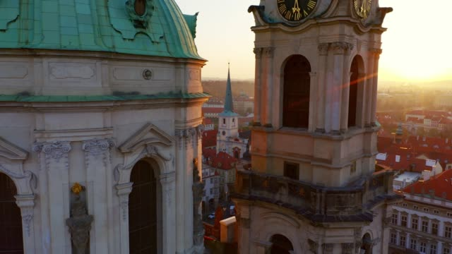 Aerial view St. Nicholas church at sunrise Aerial view St. Nicholas church in shining. Camera moving between dome and clock tower of famous cathedral, cropped view decorated building facade in backlit. Picturesque cityscape Prague at sunrise european culture stock videos & royalty-free footage