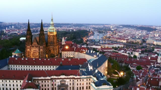 Aerial view St. Vitus Cathedral in Prague Aerial view of St. Vitus Cathedral in Prague at twilight. Drone flying at distance famous cathedral in middle of Prague castle, Lateral moving above buildings with red tiled roof at evening neo gothic architecture stock videos & royalty-free footage