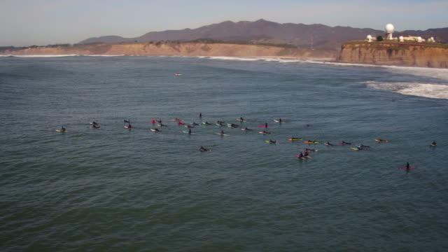 vídeos de stock, filmes e b-roll de grandes vista aérea surfistas driblando as ondas no maverick - américa do norte