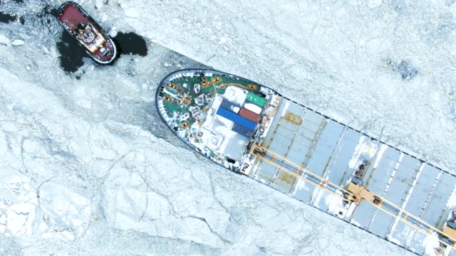 aerial view. the big ship sails through the sea ice in the winter, close-up - attrezzatura industriale video stock e b–roll