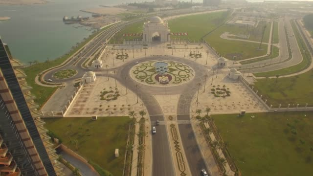 aerial view. the end of corniche road. national emblem on ground. abu dhabi. 4k - abu dhabi стоковые видео и кадры b-roll