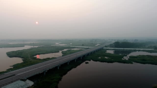 Aerial View. The picturesque landscape with river, highway bridge, trees and field with Incredible sun. Morning Fog. Aerial View. The picturesque landscape with river, highway bridge, trees and field with Incredible sun. Morning Fog. kazakhstan stock videos & royalty-free footage