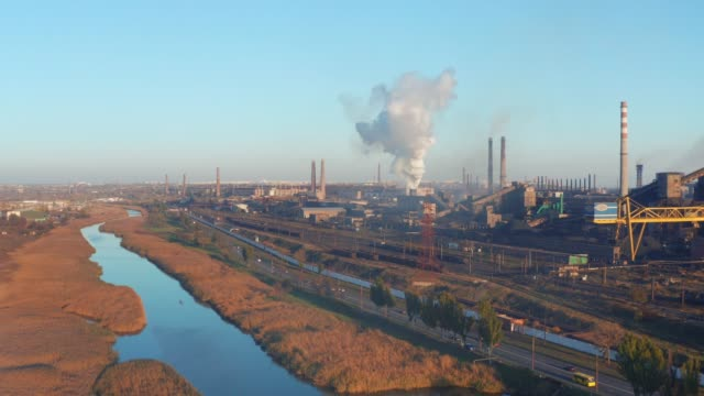 Aerial view. The river is overgrown with reeds near an industrial plant