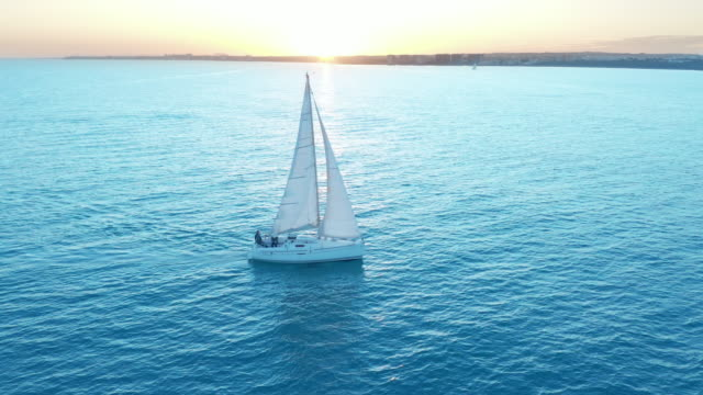 Aerial view. The yacht sails on the sea at sunset. Drone flies around the yacht with sails Aerial view. The yacht sails on the sea at sunset. Drone flies around the yacht with sails recreational boat stock videos & royalty-free footage