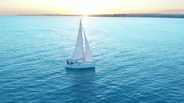 Luftbild. Die Yacht segelt bei Sonnenuntergang auf dem Meer. Drohne fliegt mit Segeln um die Yacht – Video