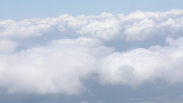 vídeos de stock e filmes b-roll de 4k. aerial view through an airplane window. beautiful white clouds in blue sky background. traveling by air. - fofo texturizado