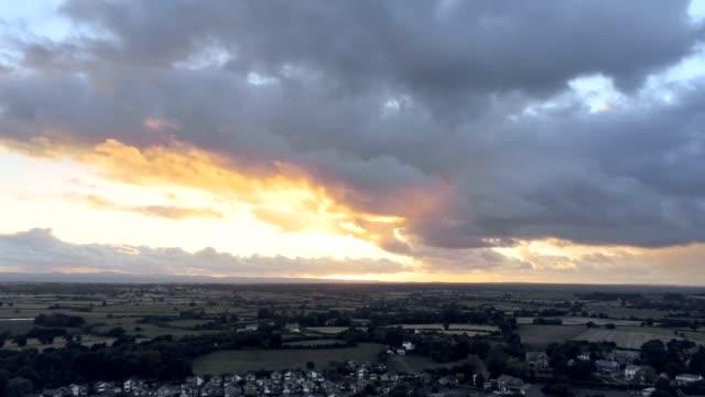 stockvideo's en b-roll-footage met luchtfoto, kantelen en opstaan verplaatsen. dramatische regenachtige hemel zonsondergang achter woonwijk van stadje, tarvin in cheshire. - regen zon