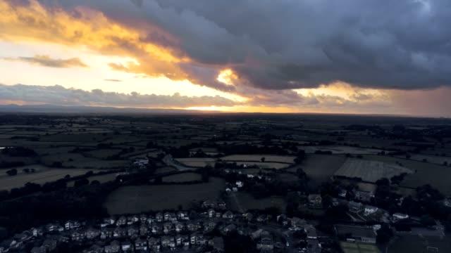 stockvideo's en b-roll-footage met luchtfoto, tilt omhoog verplaatsen. dramatic snel bewegen hemel en zonsondergang over huizen van stadje, tarvin in cheshire. - regen zon