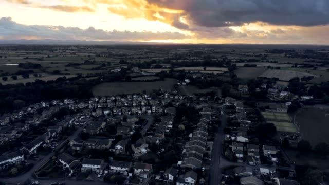 stockvideo's en b-roll-footage met luchtfoto, tilt omhoog verplaatsen. dramatische zonsondergang over woonwijk van stadje, tarvin in cheshire. - regen zon