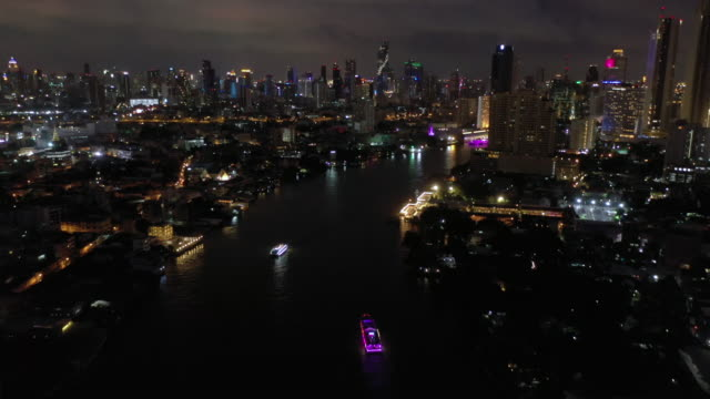 Aerial view tilt up of Chao Phraya River with Bangkok cityscape