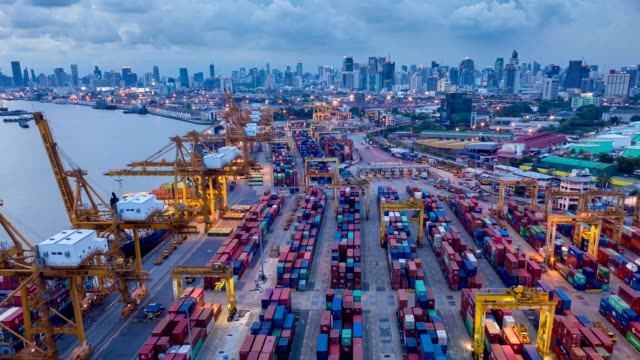 Aerial view time lapse over industrial import or export port of Thailand in Bangkok with many rows and stacks of container and big container loader ship vessel at night.