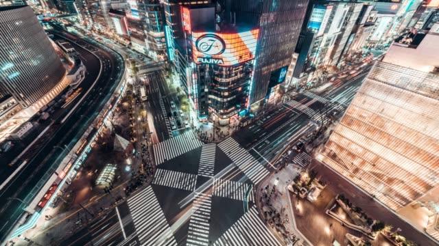 4k uhd luftbild zeitraffer der ginza straße kreuzung bei nacht, voll menschen zu fuß auf zebrastreifen und auto-ampel-strecken. asien-transport, asiatische stadtleben oder japan-tourismus-konzept - zeitraffer fast motion stock-videos und b-roll-filmmaterial