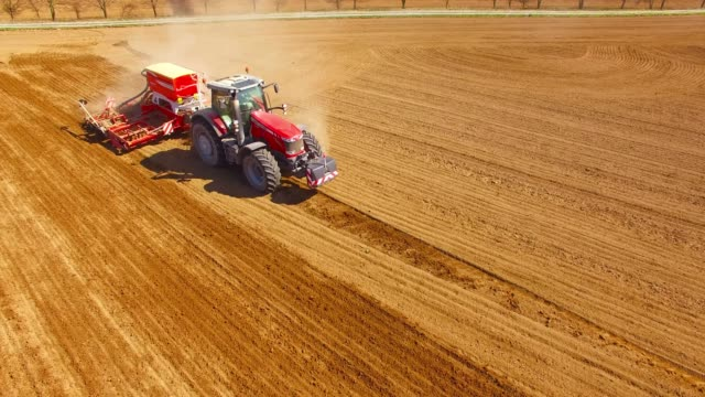Aerial view to a Tractor with sowing machine working on a  field. Agriculture from above. Aerial view to a Tractor with sowing machine working on a  field. Agriculture from above. plow stock videos & royalty-free footage