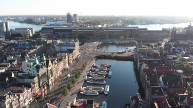 Aerial view to Amsterdam centraal station Aerial sunrise view with canal, sky and centraal station amsterdam stock videos & royalty-free footage