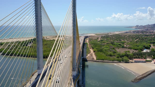 Aerial view to Natal postcard, Rio Grande do Norte, Brazil Wide angle view of Newtown Navarro bridge with drone passing trough it. natal stock videos & royalty-free footage