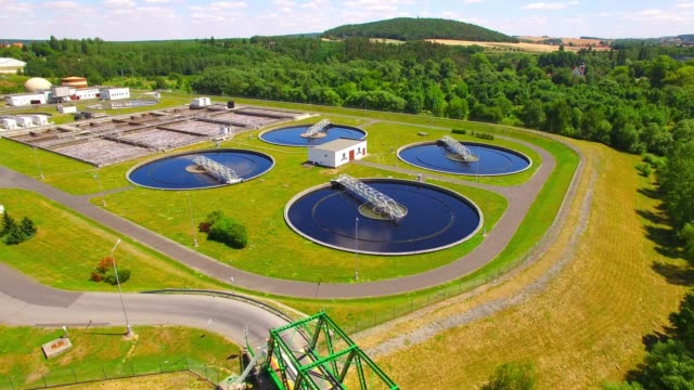 aerial view to sewage treatment plant. grey water recycling. waste management theme. ecology and environment in european union. - биомасса возобновляемая энергия стоковые видео и кадры b-roll